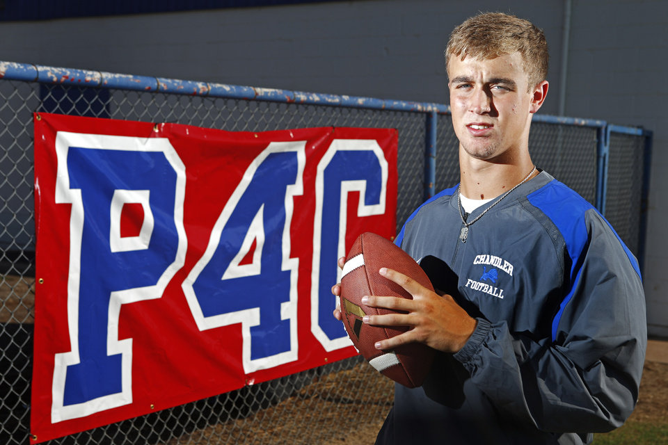 Photo - HIGH SCHOOL FOOTBALL: Chandler quarterback Mason Myers poses for a photo in Chandler, Okla., Wednesday, Sept. 18, 2013, by a sign for his father, coach Scott Myers, who passed away of cancer after last season. Photo by Bryan Terry, The Oklahoman
