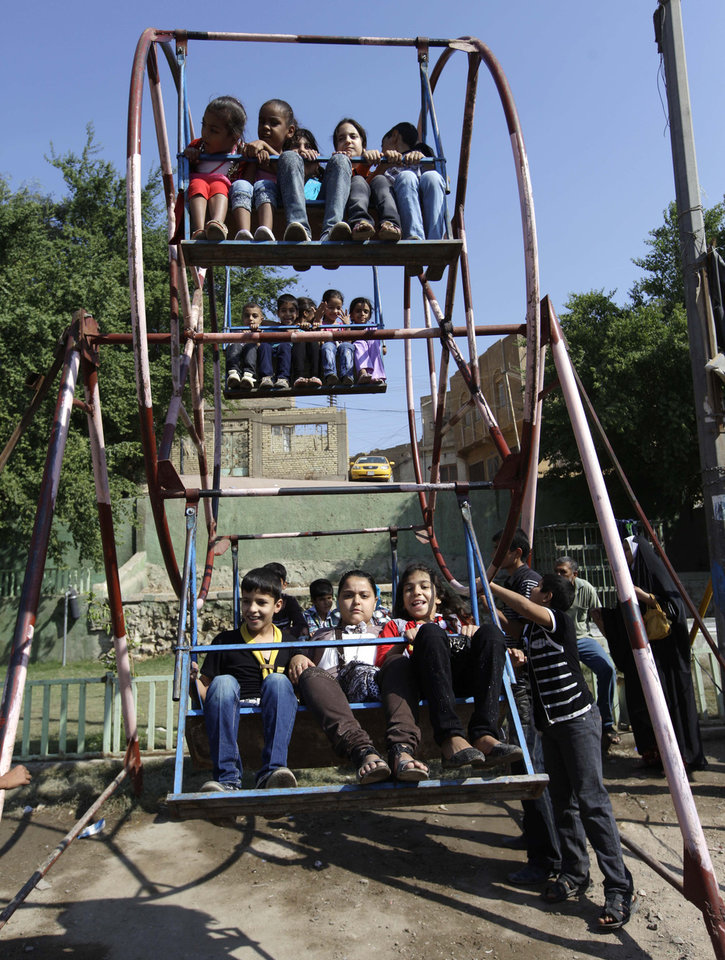 Photo -   Iraqi children play during Eid al-Adha celebrations in Baghdad's Fadhil neighborhood, Iraq, Saturday, Oct. 27, 2012. A bombing near a playground and other insurgent attacks killed 18 people including several children in Iraq on Saturday, police said. (AP Photo/Khalid Mohammed)