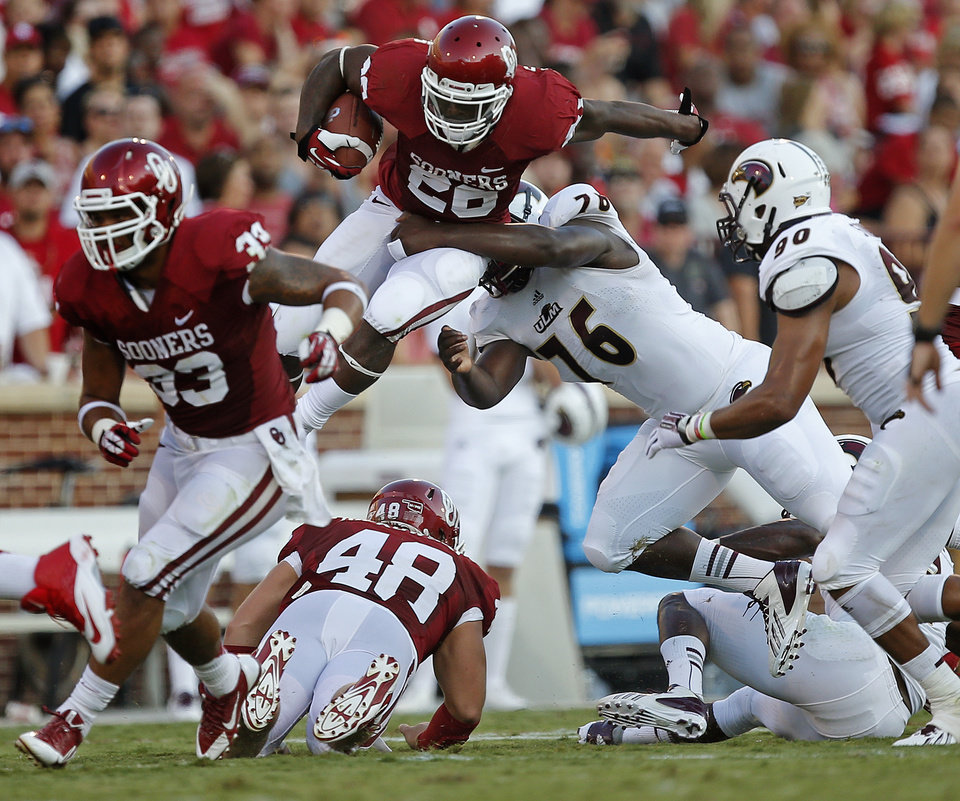 Oklahoma's Damien Williams (26) leaps over Louisiana Monroe's Gerrand Johnson (76) during a college football game between the University of Oklahoma Sooners (OU) and the University of Louisiana Monroe Warhawks at Gaylord Family-Oklahoma Memorial Stadium in Norman, Okla., on Saturday, Aug. 31, 2013. Photo by Bryan Terry The Oklahoman