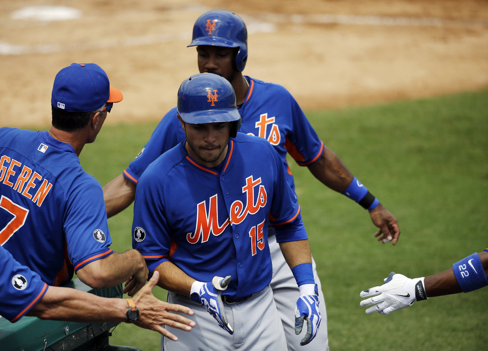 Photo - New York Mets' Travis d'Arnaud, center, is high-fived by teammates after hitting a two-run home run to score Chris Young, rear, in the second inning of an exhibition spring training baseball game against the Miami Marlins, Saturday, March 22, 2014, in Jupiter, Fla. (AP Photo/David Goldman)