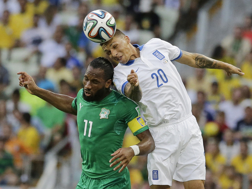 Photo - Greece's Jose Holebas heads the ball over Ivory Coast's Didier Drogba during the group C World Cup soccer match between Greece and Ivory Coast at the Arena Castelao in Fortaleza, Brazil, Tuesday, June 24, 2014. (AP Photo/Bernat Armangue)