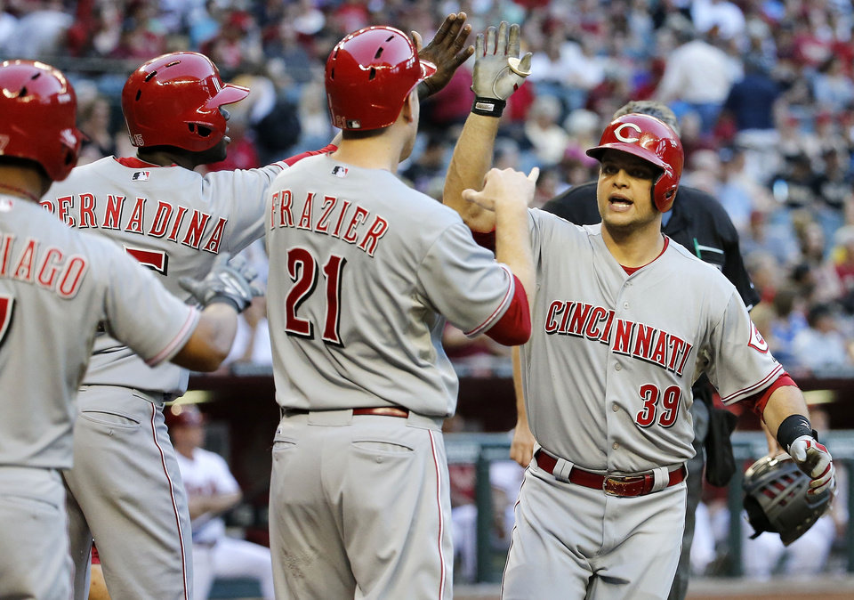 Cincinnati Reds\' Devin Mesoraco (39) is congratulated by teammates Todd Frazier (21), Ramon Santiago, left, and Roger Bernadina after hitting a grand slam against the Arizona Diamondbacks during the second inning of a baseball game, Friday, May 30, 2014, in Phoenix. (AP Photo/Matt York)