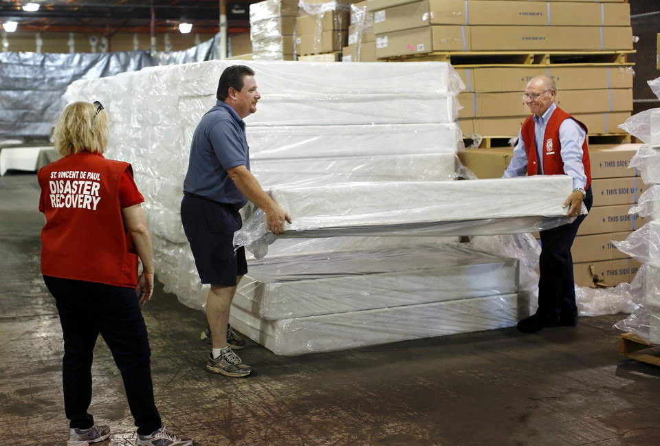 Photo - Elizabeth Disco-Shearer watches as Matt Maly, a member of the state council of the Knights of Columbus,  and Ralph Hassel, lift a mattress from a stack of bedding at a warehouse that served as a site for the