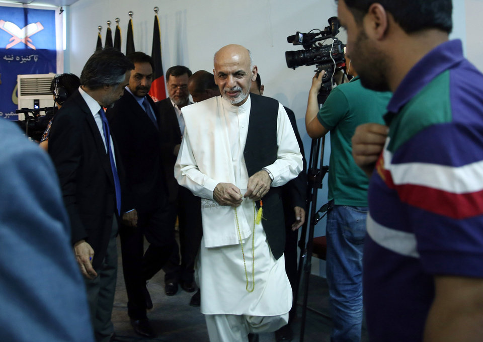 Photo - Afghan presidential candidate Ashraf Ghani Ahmadzai, center, leaves a news conference in Kabul, Afghanistan, Tuesday, July 8, 2014. The Afghan Independent Election Commission released preliminary election results Monday showing the former finance minister Ashraf Ghani Ahmadzai well in the lead for the presidency but said no winner could be declared because millions of ballots were being audited for fraud.(AP Photo/Massoud Hossaini)
