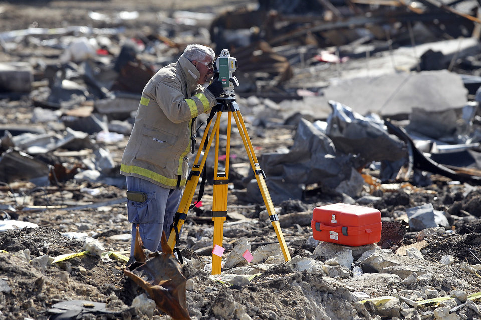 Photo - A forensic mapper works measuring the crater at the site of the fire and explosion in West, Texas on Wednesday, April 24, 2013. The explosion at West Fertilizer which killed 14 people left a crater more than 90 feet (27 meters) wide and blasted the walls and windows off dozens of buildings in the town of 2,700. (AP Photo/The San Antonio Express-News, Tom Reel, Pool)