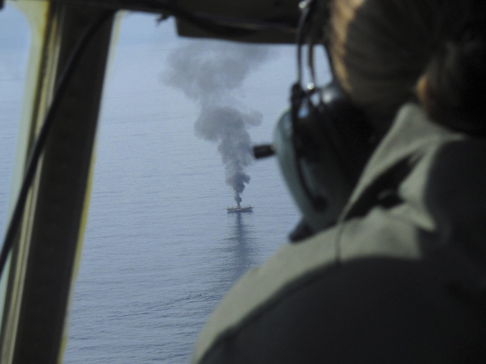 Coast Guard Petty Officer Charly Hengen, aboard a C-130, watches a giant plume of smoke rise from a derelict Japanese ship after it was hit by canon fire by a U.S. Coast Guard cutter on Thursday, April 5, 2012, in the Gulf of Alaska. The Coast Guard decided to sink the ship dislodged by last year\'s tsunami because it was a threat to maritime traffic and could have an environmental impact if it grounded. (AP Photo/Mark Thiessen)