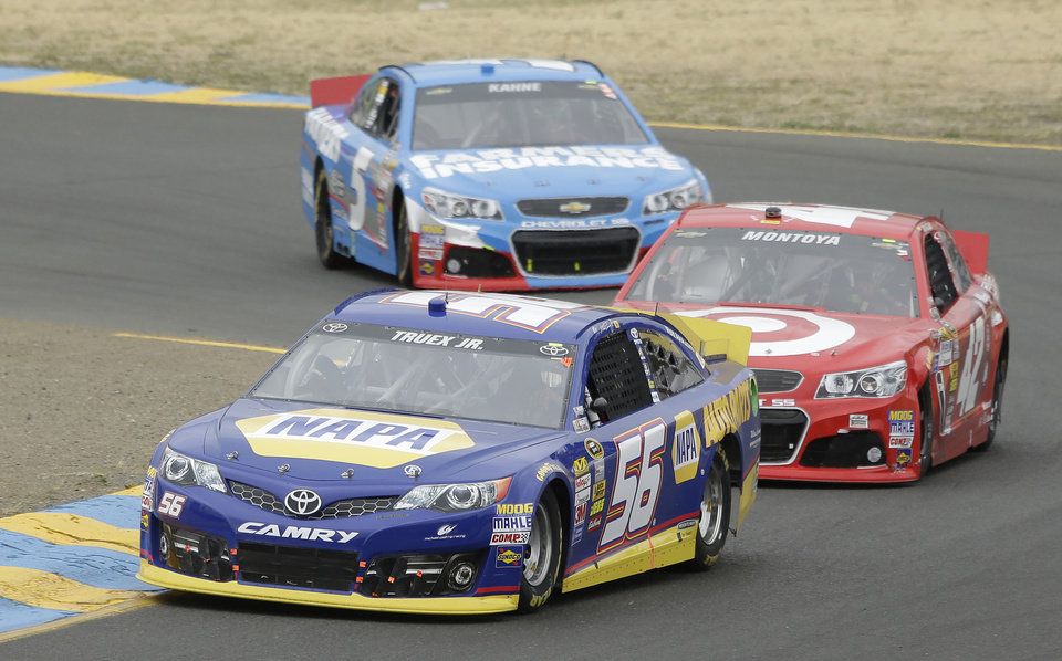 Photo - Martin Truex Jr. (56) leads Juan Pablo Montoyo, of Colombia, and Kasey Kahne through Turn 2 in a NASCAR Sprint Cup Series auto race on Sunday, June 23, 2013, in Sonoma, Calif. Truex Jr. won the race. (AP Photo/Eric Risberg)