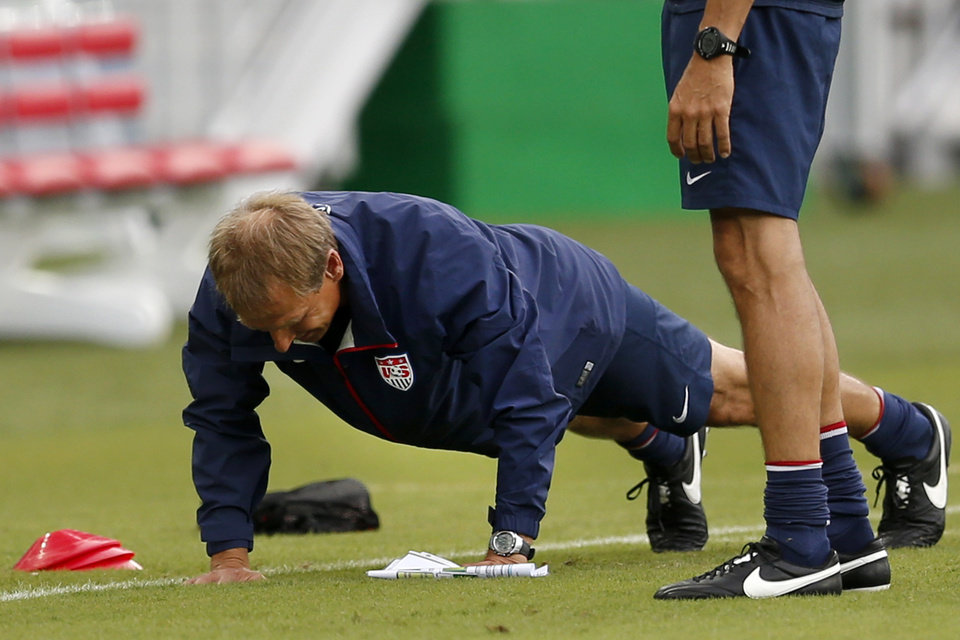 Photo - United States' head coach Jurgen Klinsmann does push-ups before an official training session the day before the group G World Cup soccer match between Ghana and the United States at the Arena das Dunas in Natal, Brazil, Sunday, June 15, 2014.  (AP Photo/Julio Cortez)