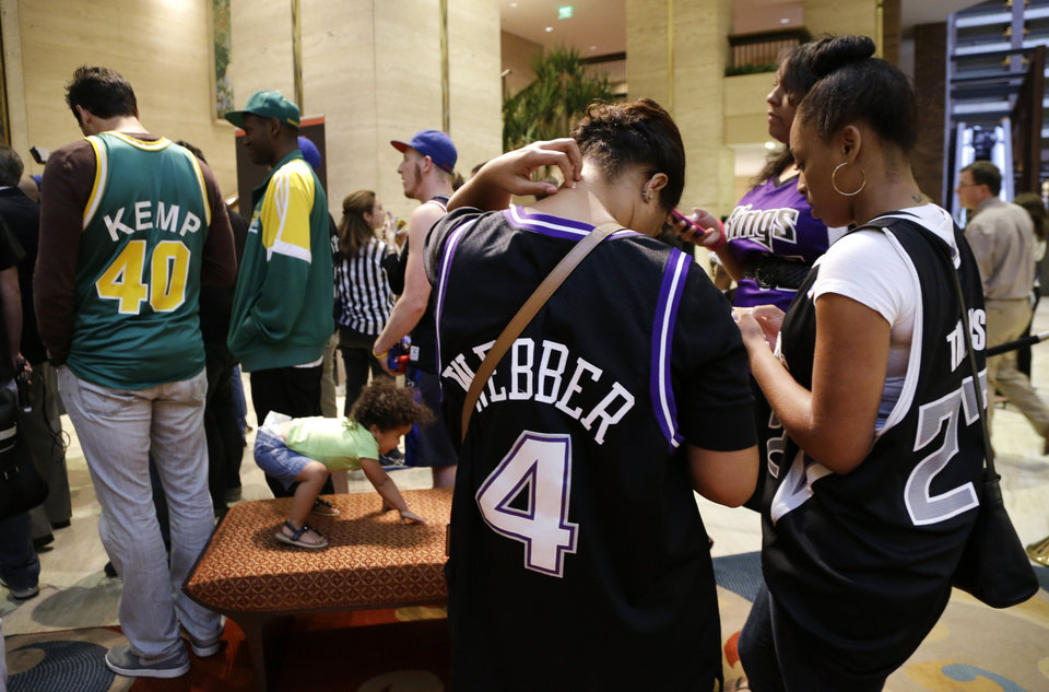 Photo - George John, left, of Seattle, wearing a Seattle SuperSonics Shawn Kemp jersey; Dominique Adams, wearing a Chris Webber Sacramento Kings jersey; and fellow supporter Brianna James, right, both of Sacramento all check their smart phones, keeping up with the latest Twitter results during the NBA Board of Governors meeting Wednesday, May 15, 2013, in Dallas. NBA owners voted Wednesday to reject the Kings' proposed move to Seattle, the latest in a long line of cities that have tried to land the franchise. (AP Photo/Tony Gutierrez)