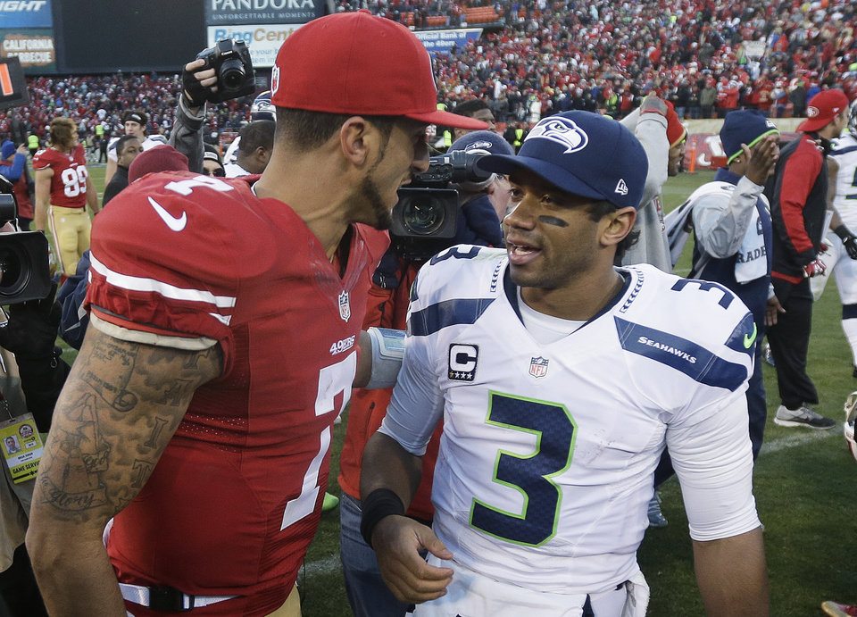 Photo - FILE - In this Dec. 8, 2013, file photo, San Francisco 49ers quarterback Colin Kaepernick, left, talks with Seattle Seahawks quarterback Russell Wilson (3) after an NFL football game in San Francisco. The 49ers beat the Seahawks 19-17. The Seahawks host the 49ers in the NFC championship on Sunday.  (AP Photo/Marcio Jose Sanchez)