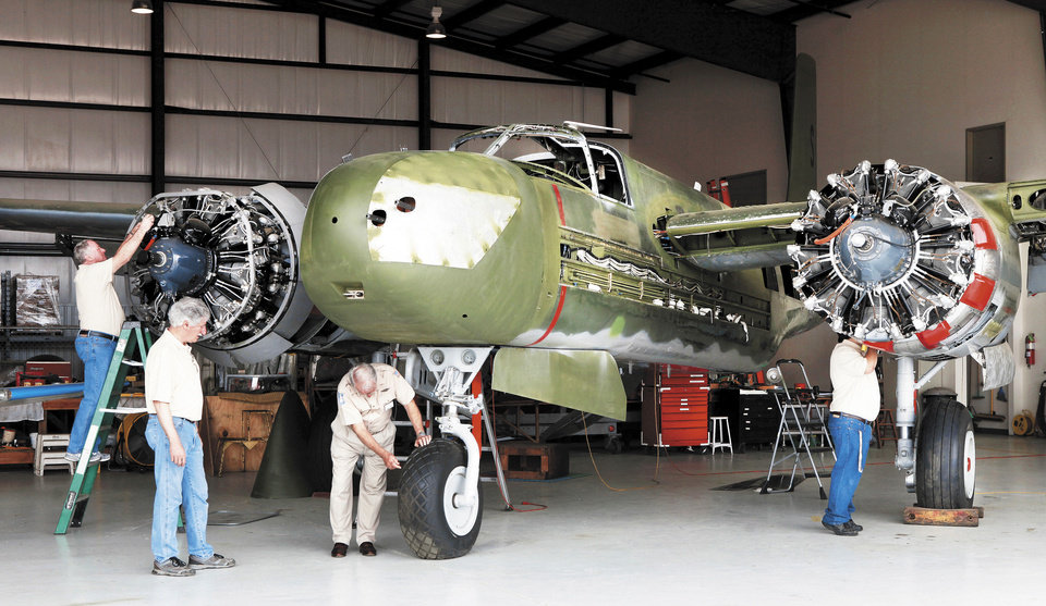 A group of men are shown Monday restoring a World War II-era A-26 bomber inside a hangar at Guthrie  Municipal Airport. Photo by Jim Beckel, The Oklahoman