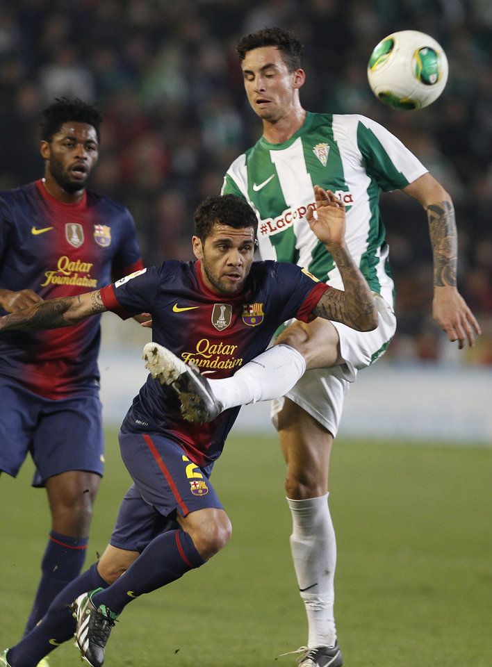 Barcelona's Daniel Alves, left, and Cordoba's Vincenzo Rennella, right, fight for the ball during the 1st leg of a last-16 Copa del Rey soccer match at Arcangel stadium in, Cordoba, Spain on Wednesday, Dec. 12, 2012. (AP Photo/Angel Fernandez)