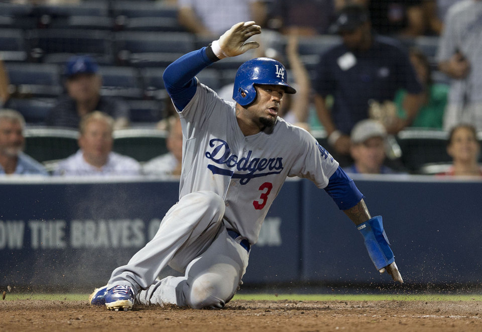 Photo - Los Angeles Dodgers' Carl Crawford (3) scores on a A.J. Ellis ground ball in the eighth inning of a baseball game against the Atlanta Braves  Monday, Aug. 11, 2014 in Atlanta.  (AP Photo/John Bazemore)
