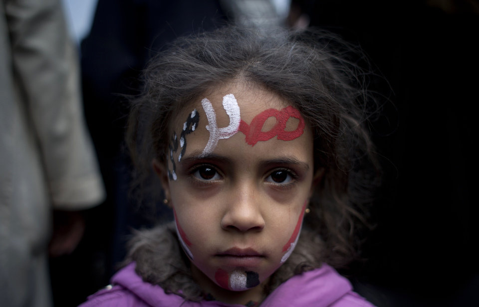 Photo - A girl with the colors of Egypt's national flag and Arabic that reads,