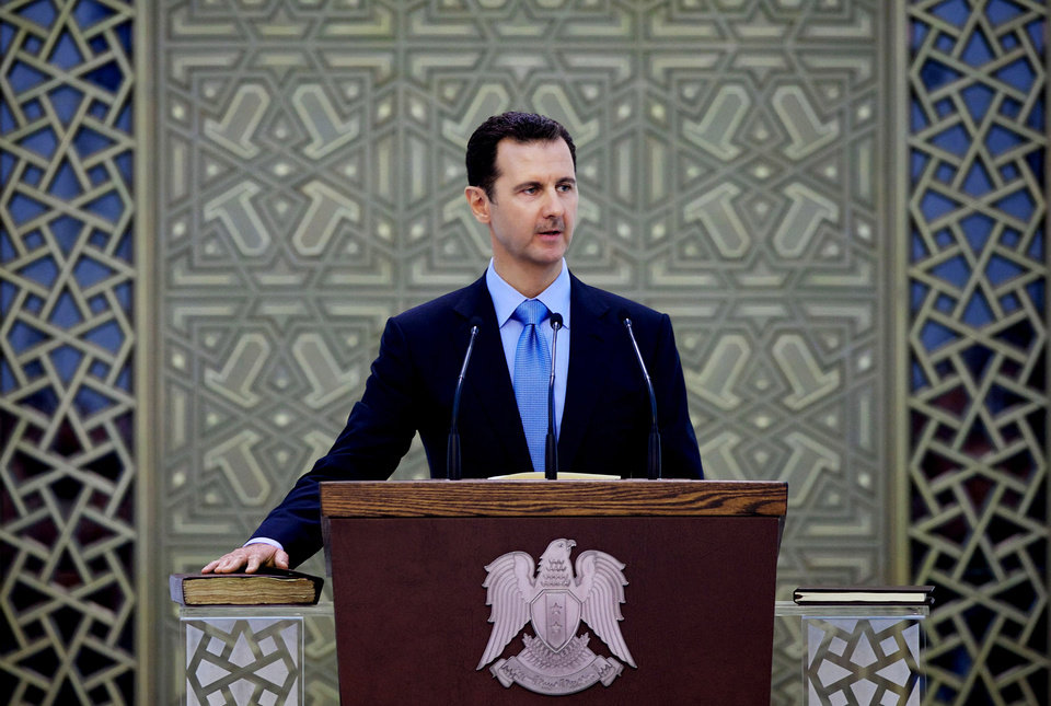 Photo - FILE - In this Wednesday July 16, 2014 file photo released by the Syrian official news agency SANA, Syria's President Bashar Assad is sworn for his third, seven-year term, in Damascus, Syria. Despite being battered by a war, now in its fourth year, the country is still firmly under the grip of President Bashar Assad despite an armed rebellion to uproot him and losing territory to opposition rebels and the extremist Islamic State group. (AP Photo/SANA, File)