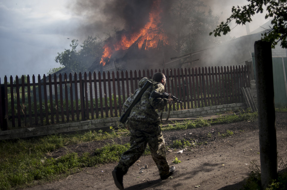 Photo - A pro-Russian armed man runs past a burning house after it was set on fire by a mortar shell, on the outskirts of the town of Lysychansk, Ukraine, on Thursday, May 22, 2014. In the eastern Luhansk region, sustained gunfire and shelling rocked the town of Lysychansk. One mortar bomb hit a house, which burst into flames. Earlier today at least 11 Ukrainian troops were killed and about 30 others were wounded during an attack at a military checkpoint, the deadliest raid in the weeks of fighting in eastern Ukraine. (AP Photo/Evgeniy Maloletka)