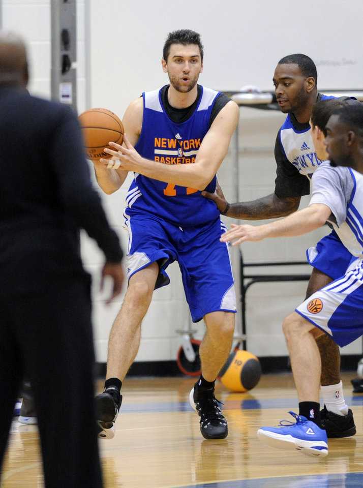 Photo - New York Knicks' Andrea Bargnani, of Italy, handles the ball as coach Mike Woodson, left, looks on during NBA basketball training camp Tuesday, Oct. 1, 2013, in Greenburgh, N.Y. (AP Photo/Bill Kostroun)