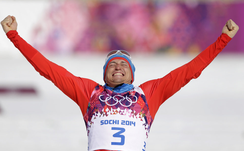 Photo - Russia's Alexander Legkov celebrates winning the gold during the flower ceremony of the men's 50K cross-country race at the 2014 Winter Olympics, Sunday, Feb. 23, 2014, in Krasnaya Polyana, Russia. (AP Photo/Matthias Schrader)