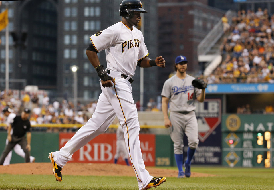 Photo - Pittsburgh Pirates' Gregory Polanco, left, is forced home from third on a bases-loaded walk by Los Angeles Dodgers starting pitcher Dan Haren (14) during the first inning of a baseball game in Pittsburgh, Wednesday, July 23, 2014. (AP Photo)