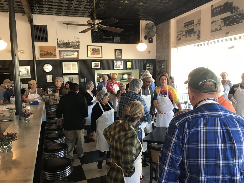 Photo -  Volunteers gather on Thanksgiving at Kaiser's Grateful Bean. [Photo by Dave Cathey, The Oklahoman]