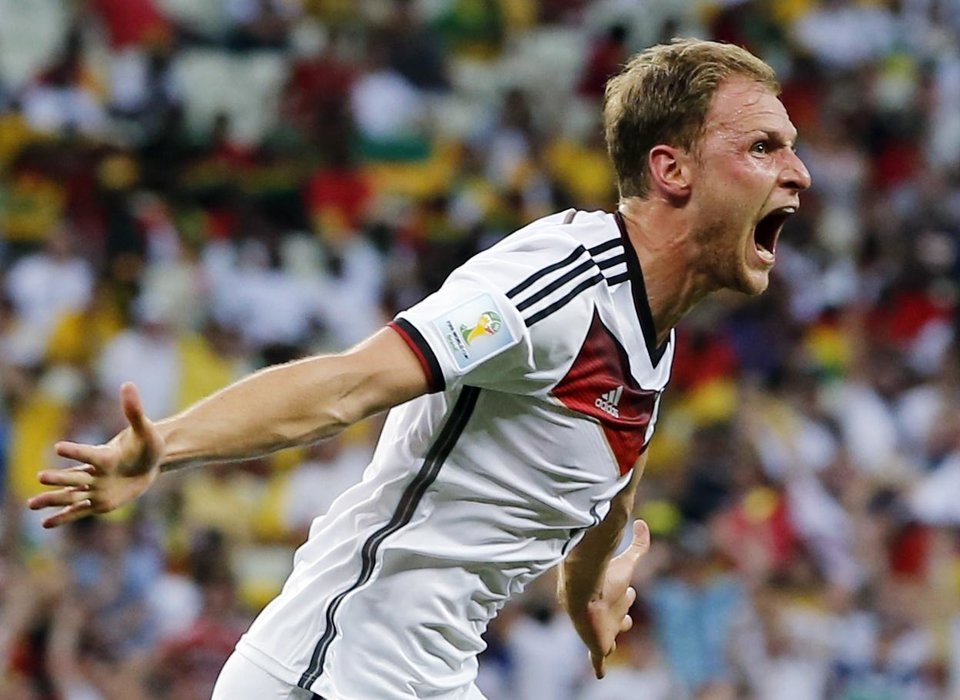Photo - Germany's Benedikt Hoewedes celebrates after his teammate Miroslav Klose scored a goal during the group G World Cup soccer match between Germany and Ghana at the Arena Castelao in Fortaleza, Brazil, Saturday, June 21, 2014.  (AP Photo/Matthias Schrader)