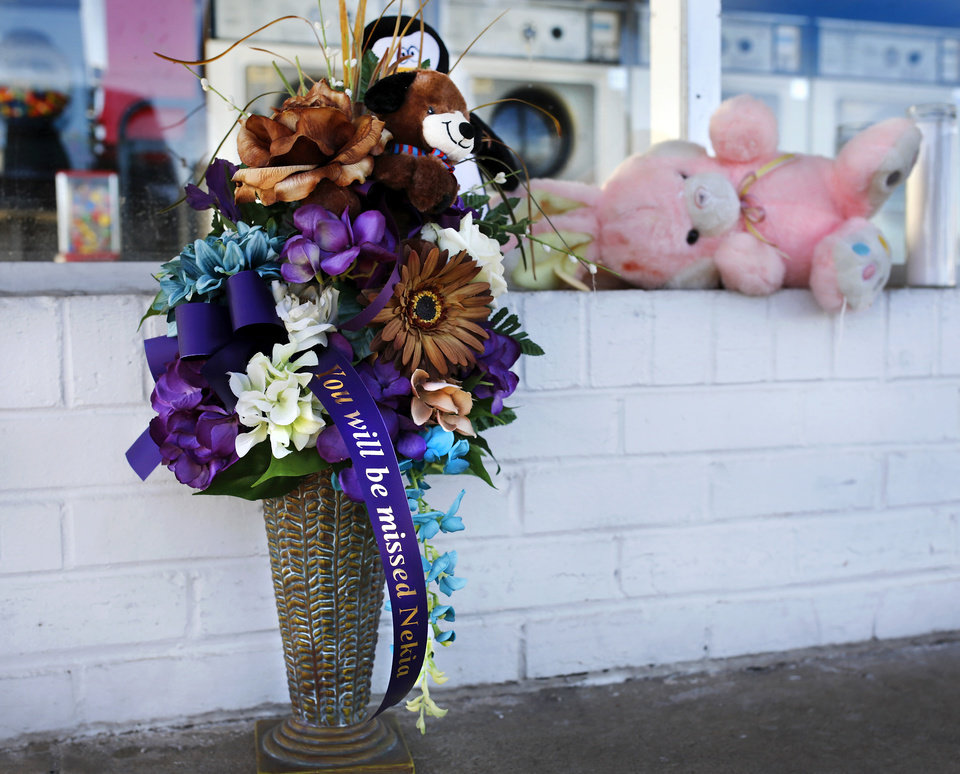 Photo - A day after two people were shot and killed at a Del City coin operated laundry business, customers and friends continue to bring items to a makeshift memorial to the woman and man who were killed yesterday inside the Laundry Station, 4000 SE 15, in Del City, shortly before it opened for business Monday.  The woman is identified as Nekia Jackson, an employee at the business. Photo by Jim Beckel, The Oklahoman