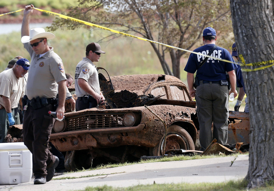 Photo - Law enforcement officials from multiple agencies examine the two cars pulled from Foss Lake, in Foss, Okla., Wednesday, Sept. 18, 2013. The Oklahoma State Medical ExaminerÂ's Office says authorities have recovered skeletal remains of multiple bodies in the Oklahoma lake where the cars were recovered. (AP Photo/Sue Ogrocki) ORG XMIT: OKSO101