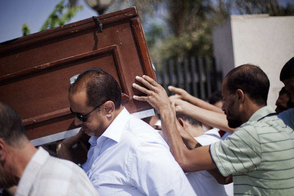 Photo - Friends and relatives of Ammar Badie, 38, killed Friday by Egyptian security forces during clashes in Ramses Square, and also son of Muslim Brotherhood's spiritual leader Mohammed Badie, carry his coffin during his funeral in al-Hamed mosque in Cairo's Katameya district, Egypt, Sunday, Aug. 18, 2013. Egypt increased security at the Supreme Constitutional Court building ahead of planned mass rallies by supporters of the country's ousted President Mohammed Morsi. (AP Photo/Manu Brabo)
