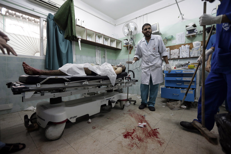 Photo - A Palestinian surgeon gives orders to hospital staff to clean the operation room as he treats a man who was wounded in an Israeli strike on a house in Beit Lahiya, in the emergency room of the Kamal Adwan hospital, in Beit Lahiya, northern Gaza Strip, Sunday, Aug. 3, 2014. (AP Photo/Lefteris Pitarakis)