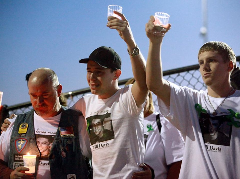 Photo -  Duncan Boatner (center), Daniel Dingal and Jeff Billingsley (left), a member of the Downed Bikers Association, lift candles during a candlelight vigil for William Davis at Mathis Skate Park in Edmond on Tuesday, Oct. 12, 2010. Davis was killed in a motorcycle accident on Oct. 9, 2010. Photo by John Clanton, The Oklahoman