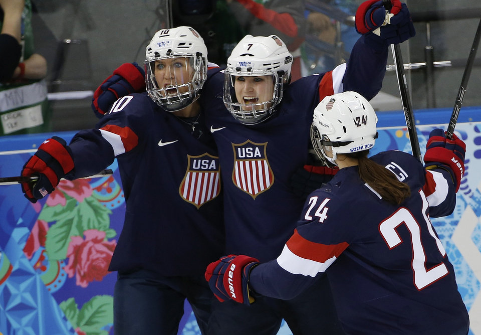 Photo - Meghan Duggan, Monique Lamoureux and Josephine Pucci of the Untied States (L-R) celebrate Lamoureux's goal against Switzerland during the 2014 Winter Olympics women's ice hockey game at Shayba Arena, Monday, Feb. 10, 2014, in Sochi, Russia. USA defeated Switzerland  9-0. (AP Photo/Petr David Josek)