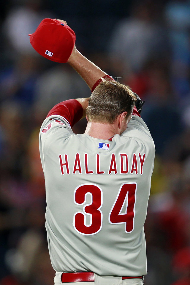 Philadelphia Phillies starting pitcher Roy Halladay (34) wipes his face before being relieved in the sixth inning of a baseball game against the Atlanta Braves in Atlanta, Wednesday, May 2, 2012. (AP Photo/John Bazemore)