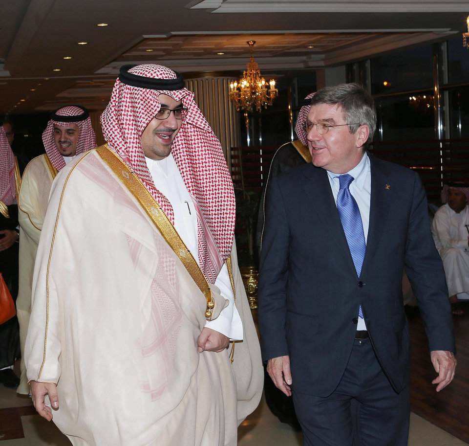 """Photo - This image released by the Saudi Press Agency shows Prince Nawaf Faisal Fahd bin Abdul-Aziz, an International Olympic Committee member and president of the national Olympic committee, left, walking with IOC President Thomas Bach, right, in Riyadh, Saudi Arabia, Wednesday, April 2, 2014. IOC President Thomas Bach has discussed the issue of women's participation in sports with Saudi Arabia's Olympic chief. The IOC says Wednesday that Bach promised """"full support"""" for the country's sports development strategy through 2020. The plan includes """"proposals to increase women's participation in the Olympic Games and in sport in general."""" Saudi women are largely banned from participating in sports in the kingdom, although there are several football and basketball clubs that play in clandestine leagues. After prolonged negotiations with the IOC, Saudi Arabia sent women to the Olympics for the first time in 2012, with two female athletes competing at the London Games. (AP Photo/Saudi Press Agency)"""