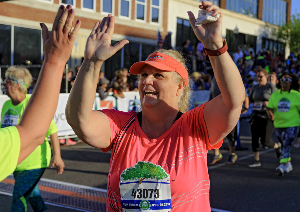 Photo - Kim Graziano is met with high-fives as she finishes the 5K race during the Oklahoma City Marathon in Oklahoma City, Okla. on Sunday, April 29, 2018.  . Photo by Chris Landsberger, The Oklahoman