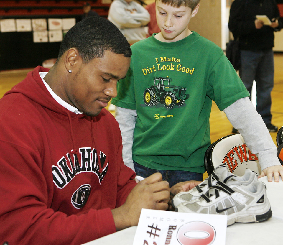 Photo - Dewar defensive back Ronnell Lewis autographs a pair of shoes for an elementary school student after Lewis signed letter of intent to play football at the University of Oklahoma during a school-wide assembly in the school's gym Wednesday morning, February 4, 2009.  BY JIM BECKEL, THE OKLAHOMAN ORG XMIT: KOD