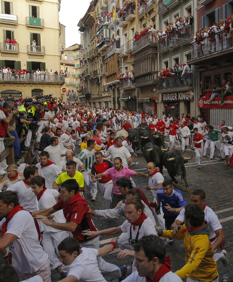 Photo - Revelers run followed by Dolores Aguirre fighting bulls during the running of the bulls of the San Fermin festival, in Pamplona, Spain, Tuesday, July 8, 2014. Revelers from around the world arrive to Pamplona every year to take part on some of the eight days of the running of the bulls glorified by Ernest Hemingway's 1926 novel