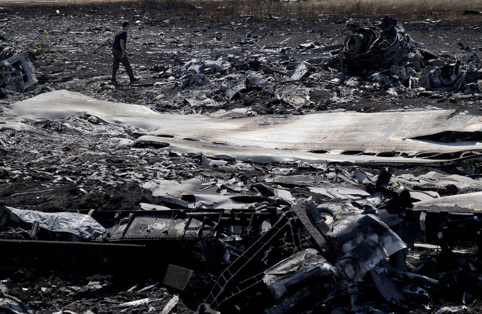 Photo - A man walks amongst charred debris at the crash site of Malaysia Airlines Flight 17 near the village of Hrabove, eastern Ukraine, Sunday, July 20, 2014. Armed rebels forced emergency workers to hand over all 196 bodies recovered from the Malaysia Airlines crash site and had them loaded Sunday onto refrigerated train cars bound for a rebel-held city, Ukrainian officials and monitors said. (AP Photo/Vadim Ghirda)