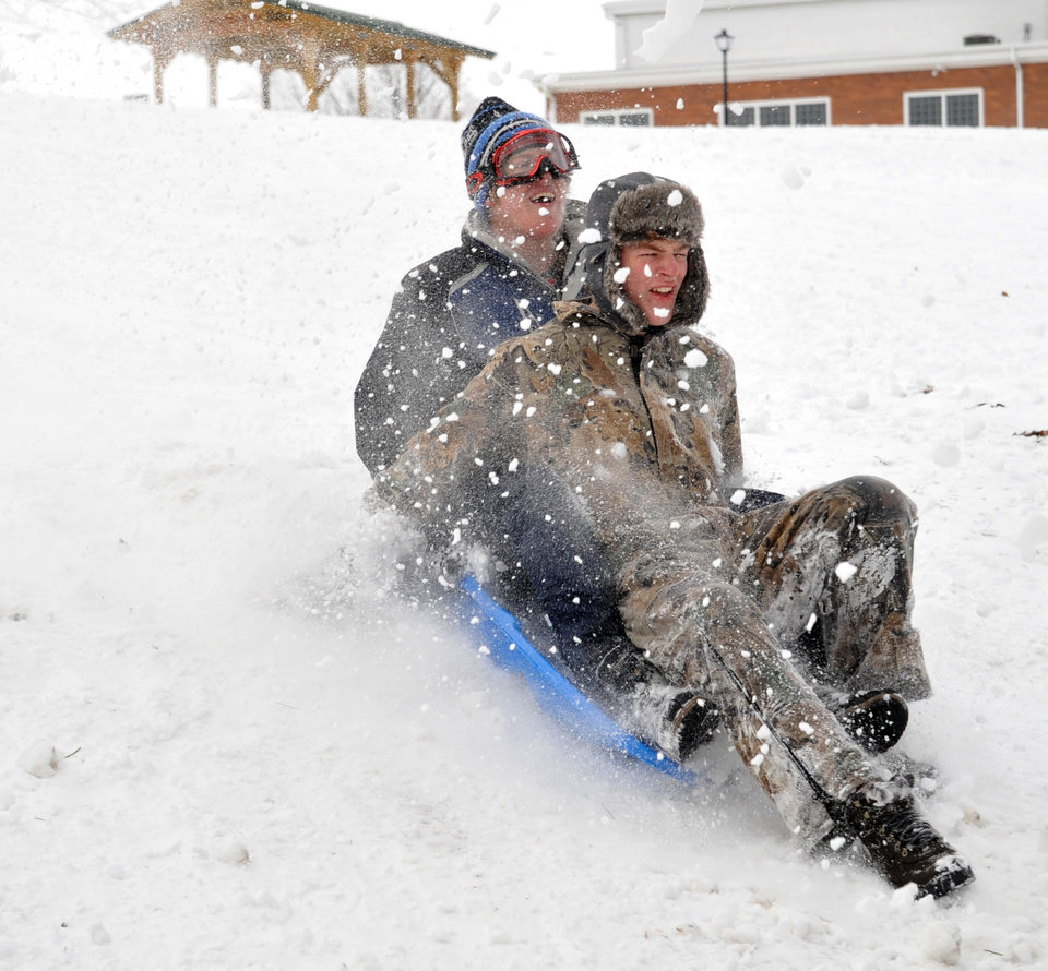 Photo - Michael Kuder, 17, of Pleasant Hill, and Luke Cameron, 16,  of Troy double up on a sled run at Mote Park in Piqua, Ohio on Thursday, Dec. 27, 2012. (AP Photo/Piqua Daily Call, Mike Ullery)