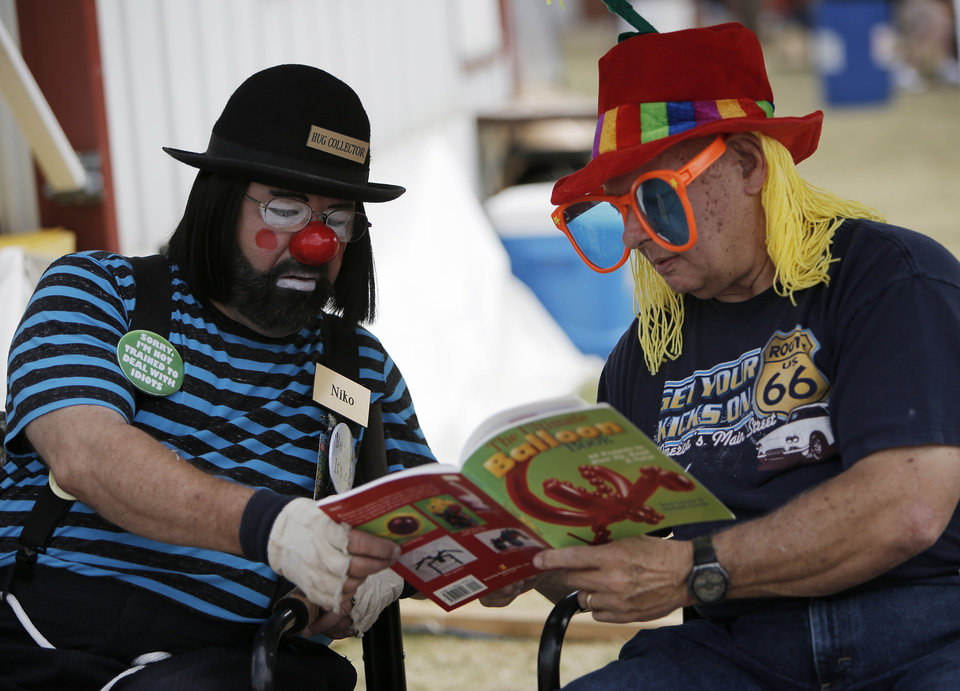 "Clowns Nick ""Niko"" Garrity and John ""Banjo"" Trivette look over a balloon book at the Oklahoma State Fair, Sunday, Sept. 23, 2012.  Photo by Garett Fisbeck, The Oklahoman"
