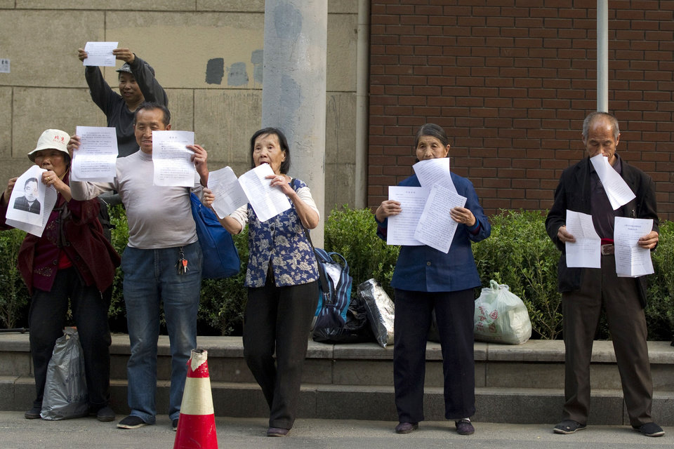 Photo -   Chinese petitioners hold up papers to attract attentions for their cases outside the hospital where blind activist Chen Guangcheng is staying for treatment in Beijing Monday, May 7, 2012. The Chinese activist who triggered a diplomatic dispute between China and the United States said Monday he was confident that Beijing would hold up its end of a tentative deal to let him study overseas. (AP Photo/Alexander F. Yuan)