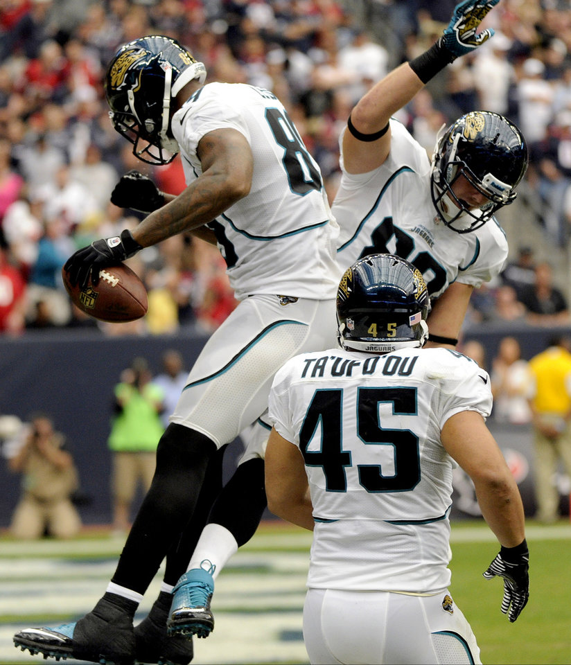 Photo -   Jacksonville Jaguars' Marcedes Lewis, left, Zach Potter, right, and Will Ta'ufo'ou (45) celebrate a touchdown against the Houston Texans during the third quarter of an NFL football game, Sunday, Nov. 18, 2012, in Houston. (AP Photo/Dave Einsel)