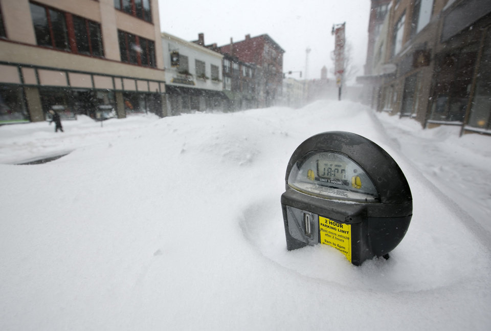 A parking meter pokes out of a snow bank during a blizzard, Saturday, Feb. 9, 2013, in Portland, Maine. The storm dumped more than 30 inches of snow as of Saturday afternoon, breaking the record for the biggest storm on record. (AP Photo/Robert F. Bukaty) ORG XMIT: MERB107