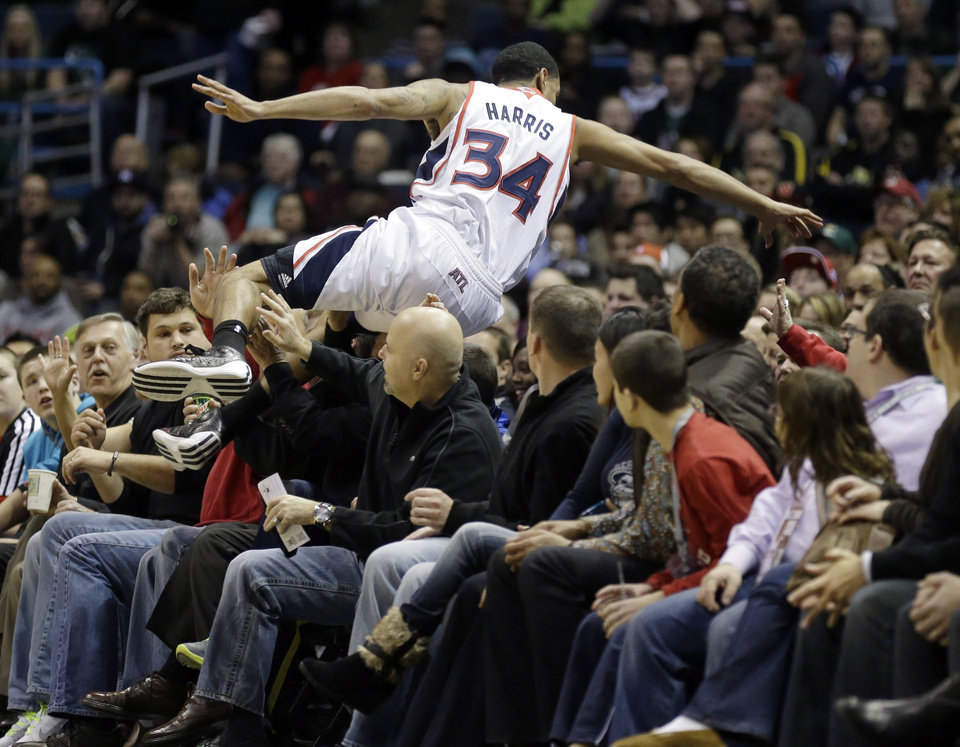 Photo - Atlanta Hawks' Devin Harris flips over fans trying to save the ball against the Milwaukee Bucks during the first half of an NBA basketball game, Saturday, Feb. 23, 2013, in Milwaukee. (AP Photo/Jeffrey Phelps)