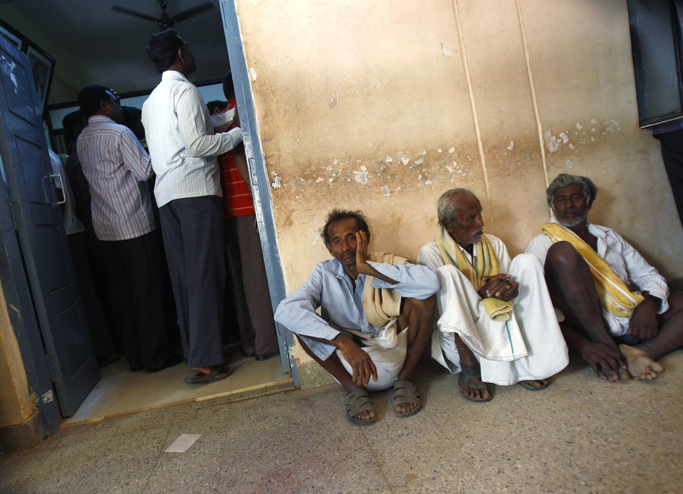 Photo - In this Dec. 10, 2012 photo, elderly villagers wait to get their land registered at the government registrar's office in Hoskote 30 kilometers (19 miles) from Bangalore in the southern Indian state of Karnataka. For years, Karnataka's land records were a quagmire of disputed, forged documents maintained by thousands of tyrannical bureaucrats who demanded bribes to do their jobs. In 2002, there were hopes that this was about to change. (AP Photo/Aijaz Rahi)