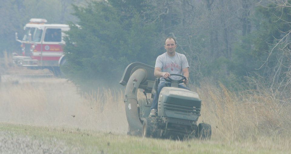 Photo - A man mows near the road as Firecrews monitor a grass fire as it approaches from the east towards Hill Top Road and 149th ave. Fri. April 10, 2009. Photo by Jaconna Aguirre, The Oklahoman.