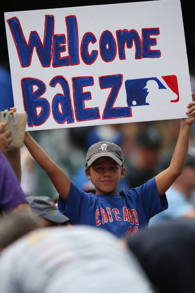 Photo - A young fan of the Chicago Cubs holds up placard to welcome the Cubs second baseman Javier Baez who was about to play in his third game since being called up from the Cubs farm team in Iowa as the Cubs face the Colorado Rockies in  a baseball game in Denver on Thursday, Aug. 7, 2014. (AP Photo/David Zalubowski)