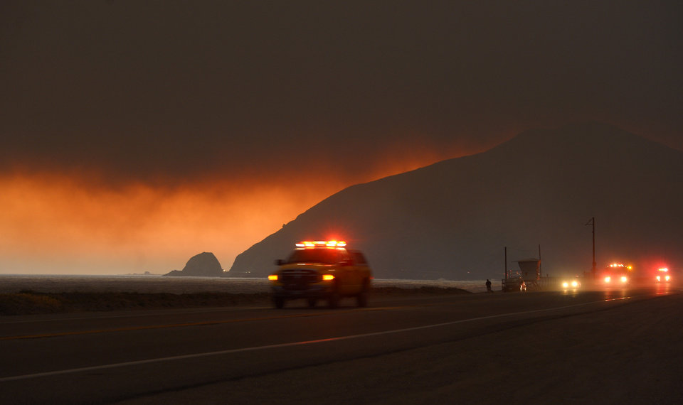 Photo - Fire department personnel drive along Pacific Coast Highway near Point Mugu as a thick layer of smoke sits overhead during a wildfire that burned several thousand acres, Thursday, May 2, 2013, in Ventura County, Calif.   (AP Photo/Mark J. Terrill)