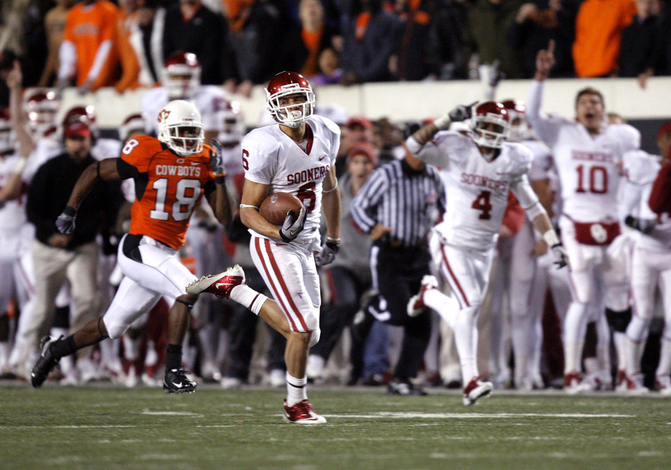 Photo - Oklahoma's Cameron Kenney  (6) scores a long touchdown as Oklahoma State's Devin Hedgepeth (18) chases him down during the Bedlam college football game between the University of Oklahoma Sooners (OU) and the Oklahoma State University Cowboys (OSU) at Boone Pickens Stadium in Stillwater, Okla., Saturday, Nov. 27, 2010. Photo by Sarah Phipps, The Oklahoman