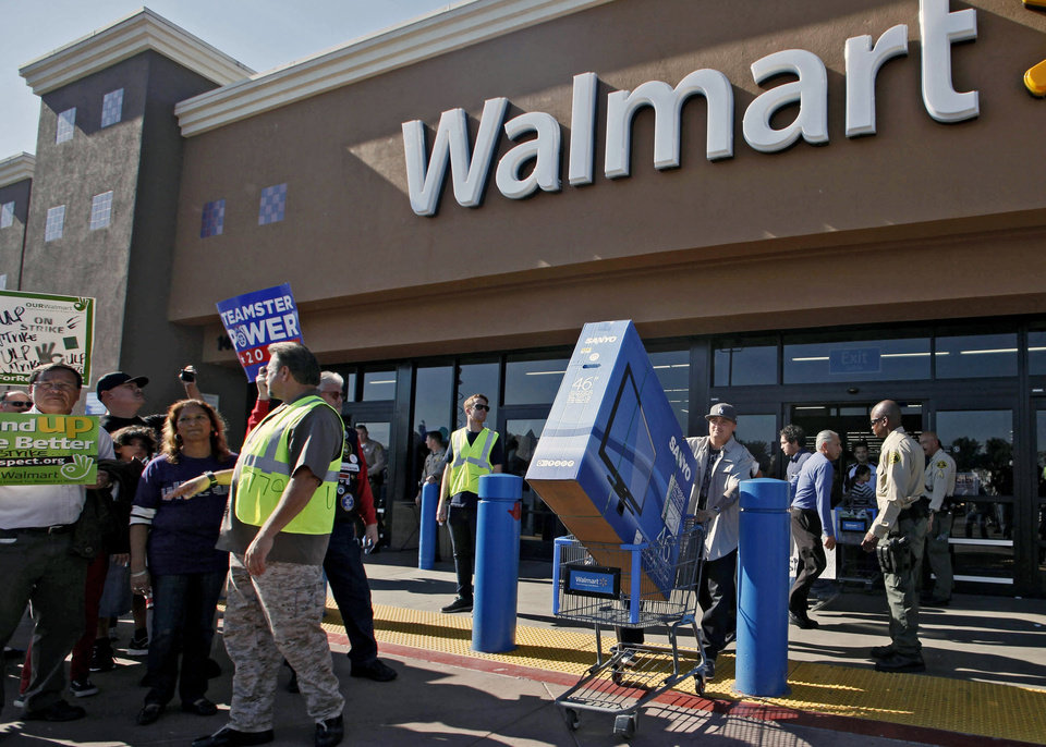Photo -   Shopper Jose Alvarez, right, carries out a newly-purchased television past protestors outside a Walmart store Friday Nov. 23, 2012, in Paramount, Calif. Wal-Mart employees and union supporters are taking part in today's nationwide demonstration for better pay and benefits A union-backed group called OUR Walmart, which includes former and current workers, staged the demonstrations and walkouts at hundreds of stores on Black Friday, the day when retailers traditionally turn a profit for the year. (AP Photo/Nick Ut)