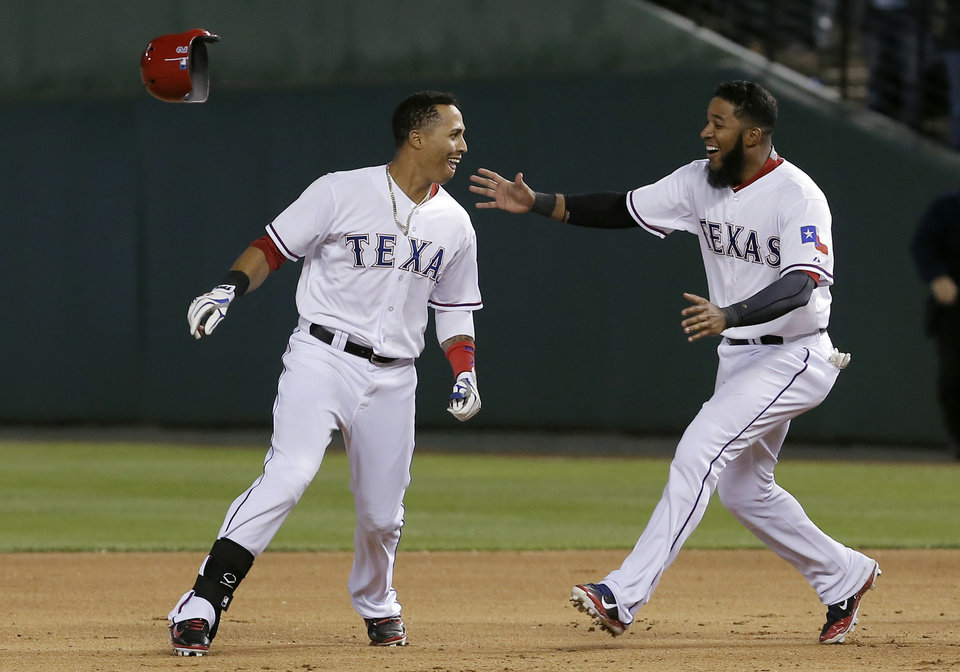 Photo - Texas Rangers Leonys Martin, left, is congratulated by teammate Elvis Andrus after hitting an RBI-single to win in the ninth inning of a baseball game against the Seattle Mariners, Wednesday, April 16, 2014, in Arlington, Texas. Texas won 3-2. (AP Photo/Brandon Wade)